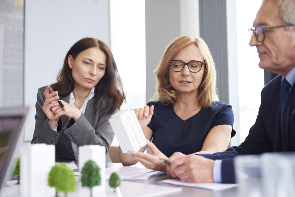 two women reviewing a proposal presented by a representative from the Cacoeli real estate investing company