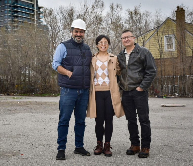 Jed and Kasey standing with a developer at the location of one of the properties owned by Cacoeli real estate investment and asset management